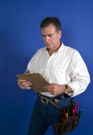 toolbelt: A man with a toolbelt around this waist looking at something on a clipboard.
