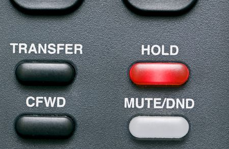 devise: Macro shot of a telephones feature buttons with the hold button red and activated.