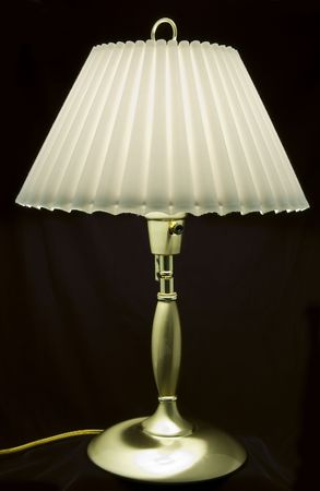 A picture of a lovely little brass lamp taken against a black backdrop.  Imagens