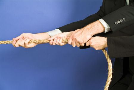 concept photo of business people using a rope as teamwork.
