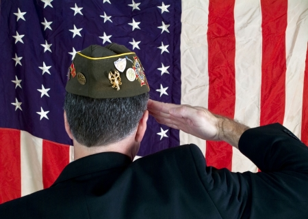 A Veteran wearing a decorated cap, saluting the American Flag.