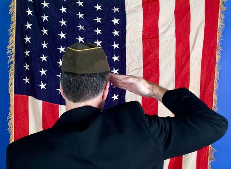 A veteran wearing his faded cap saluting the American flag