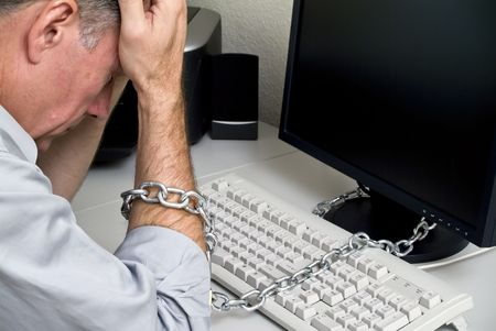 A man feeling as if he is chained to his computer doing a job with no future.