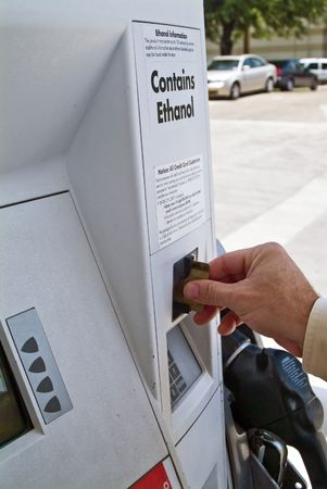 A man using the credit card scanner at a gas station fuel pump