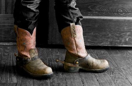 A person standing in fron of an open door, wearing a decorative pair of boots with spurs.