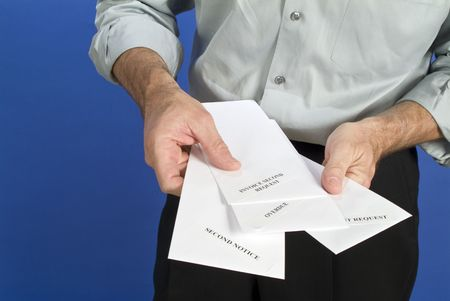 A man holding a several white envelopes with pastdue notices on them.