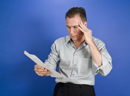 tardy: A man with a worried expression on his face holding serveral envelopes in his hand.  Stock Photo