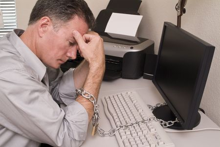 stagnate: A man chained to his computer with an expression of fatigue or intense boredom.