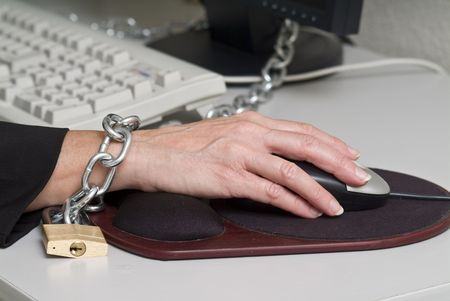 tedious: close-up of a woman chained to her desk Stock Photo