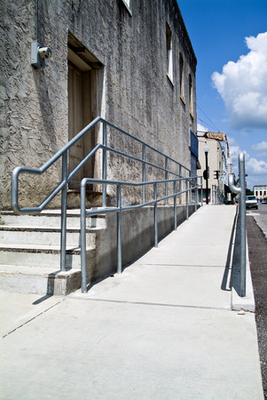 A ramp and railings built to avail easy access to a building for the physically challenged.  photo