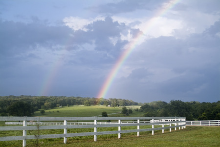 A country landscape with two rainbows accenting the during a break in the weather.