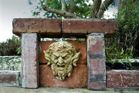 disdain: A pitted plaster devilish face attached to a brick structure.  Stock Photo