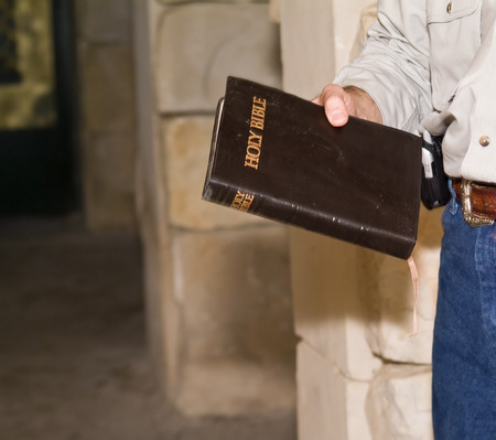 A man within room of stone walls holding a bible. 版權商用圖片 - 1439107