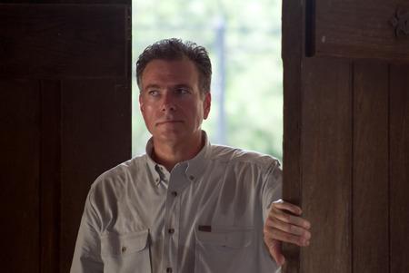 przewidywanie: Człowiek otwarcie dużych drzwi drewniane z wyglądu przewidywanie na twarz. Zdjęcie Seryjne