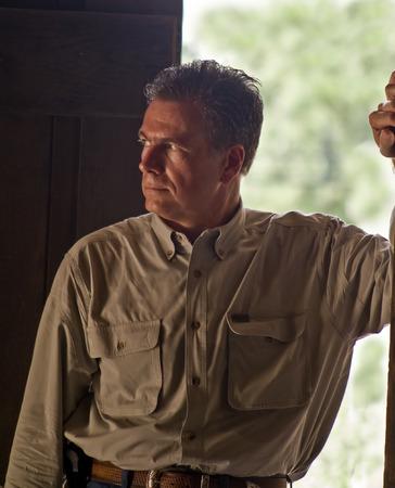 A man standing in the open door of a dark room.