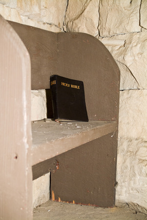 pew: A bible left behind on an old dusty pench or church pew.
