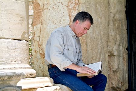 A man sitting on a stone wall reading what appears to be a bible.