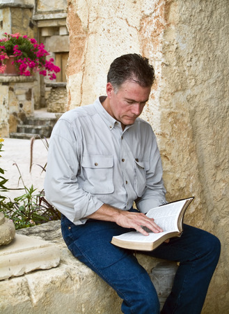 appears: A man sitting and reading what appears to be a bible.  Stock Photo