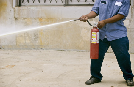 safety: A man demonstrating how to use a fire extinguisher during a fire safety practice session.