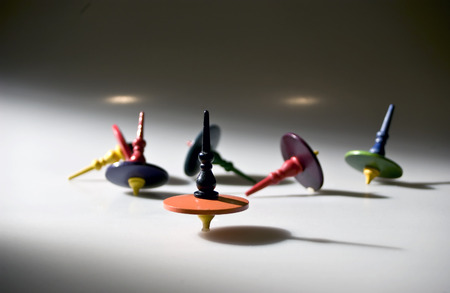 Group of toy tops light from the side. Focus is on the front orange top