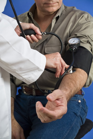 devise: A man having his blood pressure taken by a person in a white lab coat.