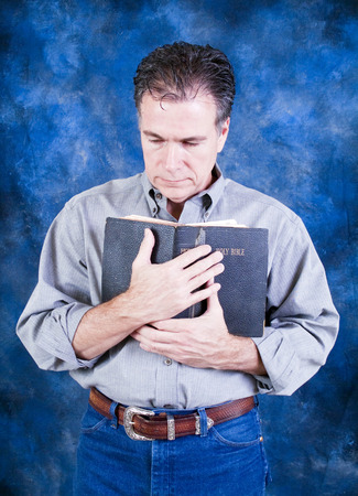 A man standing and tenderly holding an old bible to his chest.