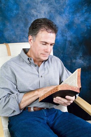 A man siting and enjoying reading what appears to be a bible.
