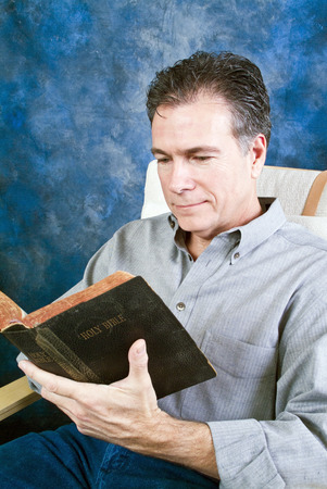 pleasant: A man with a relaxed, pleasant expression on his face reading from an old bible.  Stock Photo