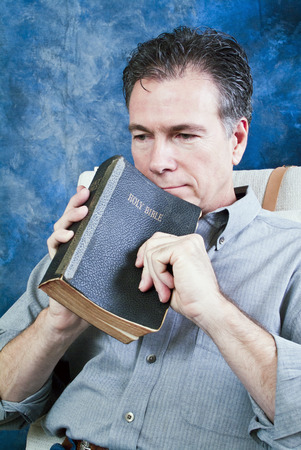 A man holding an old bible, with an expression of contemplation on his face. Stock Photo