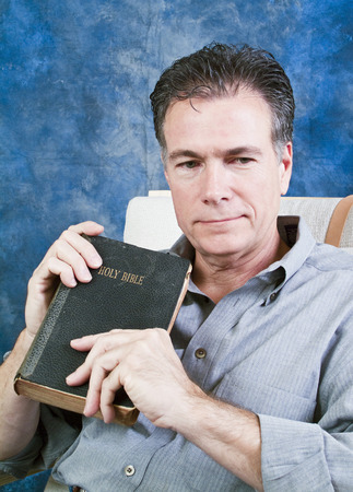 observe: A man holding an old bible, with a pensive expression on his face.