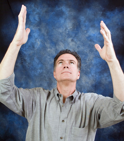 adulation: A man looking upward with his hands held high as if in a posture of prayer. Stock Photo