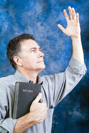 stimulated: A man in a posture of praise and worship with an old bible held tightly to his chest.  Stock Photo