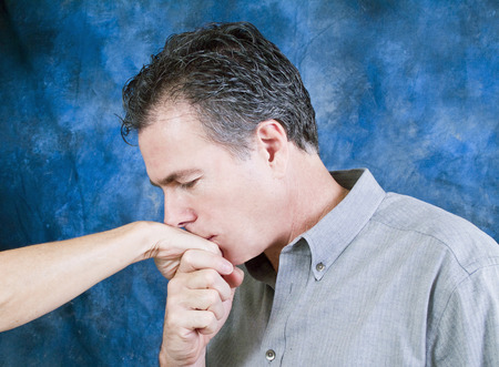 tenderly: A man tenderly kissing the hand of a woman.