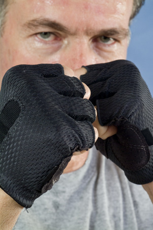 steely: A man with his fists held high in a posture of preparedness for a fight. (focus is on fists) Stock Photo