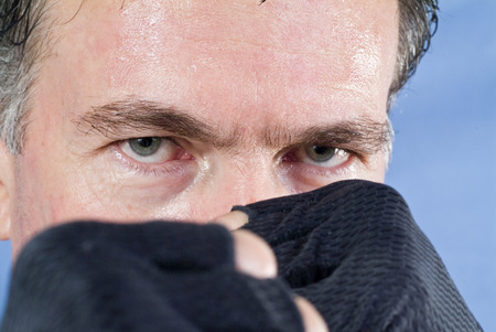 unyielding: A man with his glove covered fists held in front of his face in defense mode.  Stock Photo