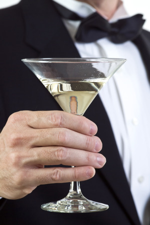 A close up of a mans hand who is dressed in formal attire and holding a martini glass.