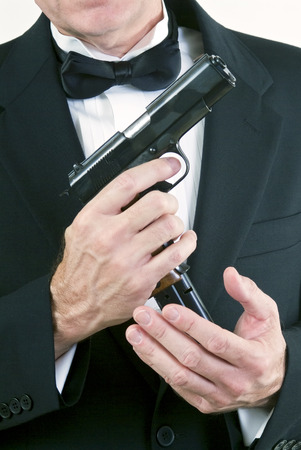 finger on trigger: Close up of a man in formal attire, loading his automatic weapon taken agains a white background.  Stock Photo