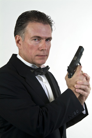 finger on trigger: A man in formal attire holding an automatic pistol taken against a white background.