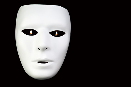 full face: A full face white mask taken on a black background with tiny flames visible through the eyes.  Stock Photo