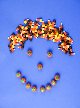 arranged: A smily face made with candy, with candy corn hair taken on a blue background.