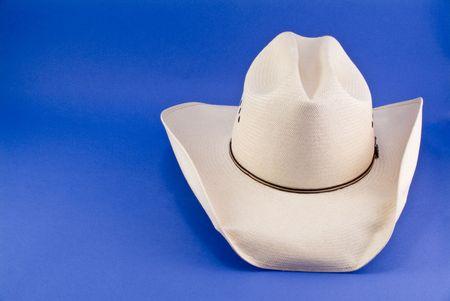 A straw cowboy hat taken on a blue background.