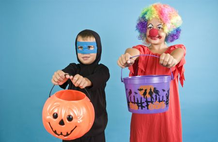 Two children holding out their Halloween containers as if ready to receive candy.