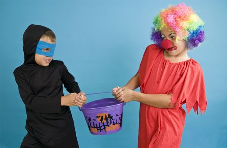 Two children fighting over a bucket with Halloween decorations on it.
