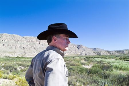 types of cactus: A man in a black cowboy hat looking out at the expanse before him.  Stock Photo