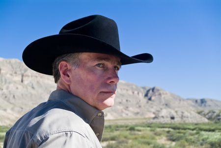rugged terrain: A portrait man in a black western style hat with cliffs and a bright blue sky in the background. Stock Photo