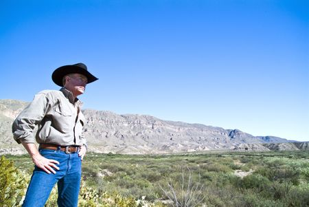 expansive: A man surveying the expansive and rugged territory surrounding him.  Stock Photo