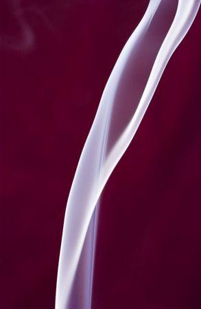深紅の背景にやさしく立ちのぼる煙の乳白色の白い噴煙。 写真素材