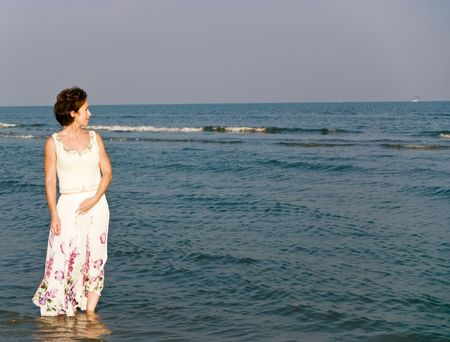A woman in a long skirt wading in the water along the beach shoreline.  Stock Photo - 1990412
