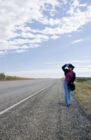 A woman standing by the side of the road holding on to her hat to keep it from blowing off.  Stock Photo
