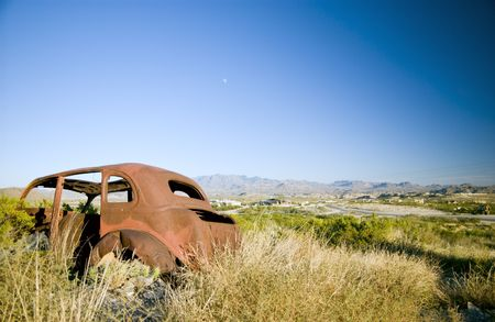 harsh: An old, long abandoned vehicle, rusting away in a very rugged, harsh environment.